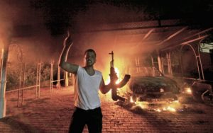 A protester reacts as the U.S. Consulate in Benghazi is seen in flames during a protest by an armed group said to have been protesting a film being produced in the United States September 11, 2012. An American staff member of the U.S. consulate in the eastern Libyan city of Benghazi has died following fierce clashes at the compound, Libyan security sources said on Wednesday. Armed gunmen attacked the compound on Tuesday evening, clashing with Libyan security forces before the latter withdrew as they came under heavy fire. REUTERS/Esam Al-Fetori (LIBYA - Tags: POLITICS CIVIL UNREST TPX IMAGES OF THE DAY)